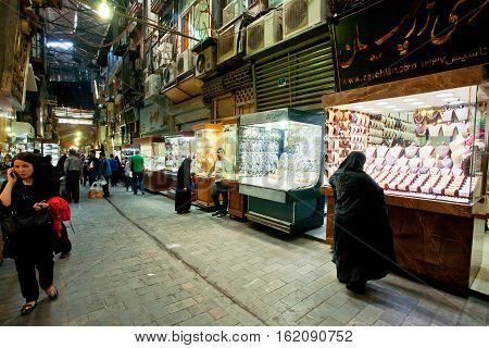 TEHRAN, IRAN - Oct 25, 2014: Muslim woman considering a showcase of jewelery at the covered bazaar on October 25, 2014. With a population of 8.3 million Tehran is the largest city in Western Asia.