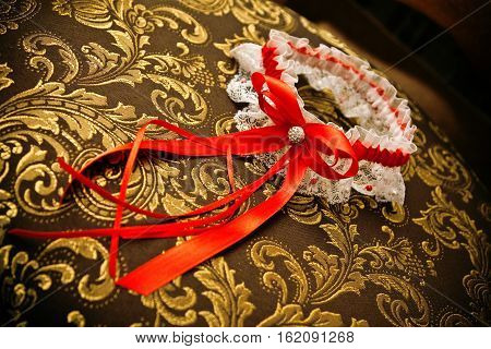 Bride's garter with red ribbon on the chair