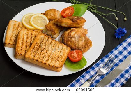 Fish in batter with croutons grilled. Wooden background. Top view