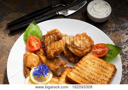 Fish in batter with croutons grilled. Old background