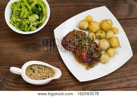 Pork medallions in mushroom sauce with new potatoes. Restaurant supply. Wooden table