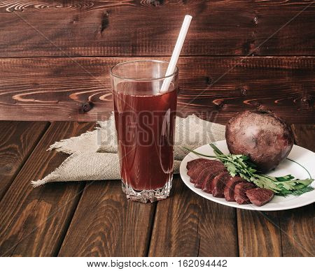 glass of fresh beet juice, dish with beets and greens on a dark rustic wooden background