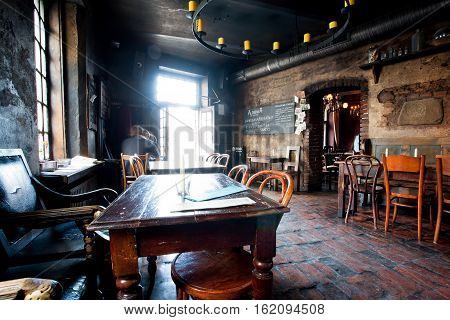 KRAKOW, POLAND - JUL 31, 2014: People indside the gothic style dark restaurant with bright light from door on July 31, 2014. Krakow with popul. of 800000 people has 2.35 mill. foreign tourists annually.