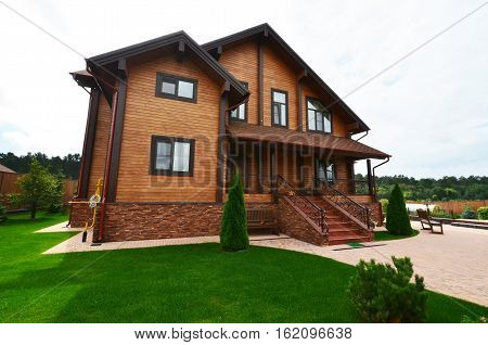 Wooden house of the profiled bars on the plot with landscape design. Russia.