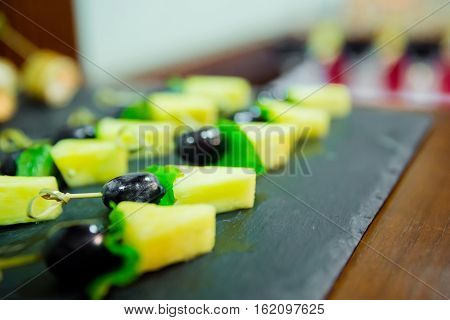 Blured cater canapes with pinapple and grapes on black table