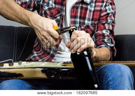 Opening beer with pliers. Male person in casual wear changing strings on electric guitar opens a bottle of drink with tool to have a break