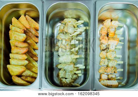 Catering cooking skewers of chicken and fish cake snack pie in a metal plate