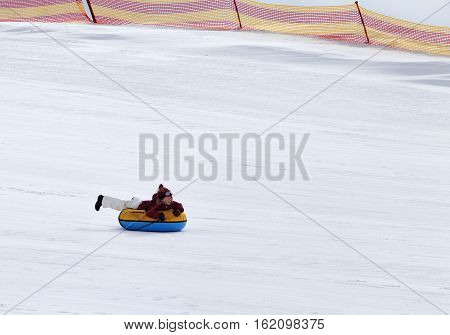 Snow tubing in ski resort at gray day