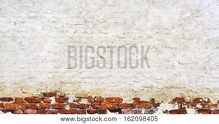 Old Vintage Red Brick Wall With Crashed White Plaster Texture Background. White Red Retro Wallpaper. Graffiti Brickwal.