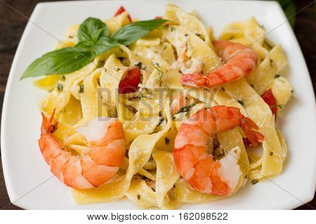Fettuccine pasta in cream sauce with king prawns on a plate on the wooden table. Horizontal view from above