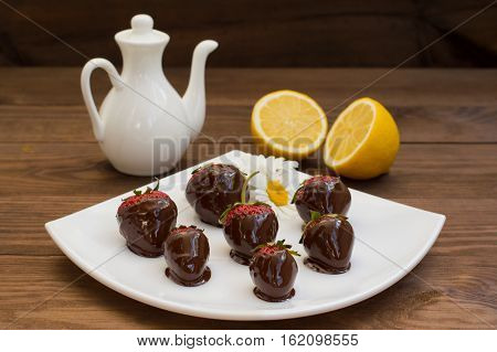 Strawberries dipped in chocolate on a white square plate. Wooden background