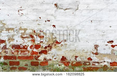 Old Brick wall with white uneven stucco. Red white wall Background. Shabby building facade.