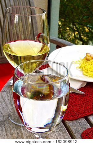 White wine and pasta served on bistro table