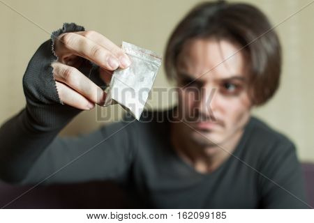 Man with cocaine dose in hand.