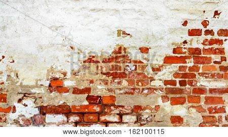 Brick wall with white uneven stucco. Red white wall Background. Old Vintage Red Brick Wall With Crashed White Plaster Texture Background.