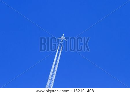 the plane flies on the surface of the blue sky leaving a white trail air