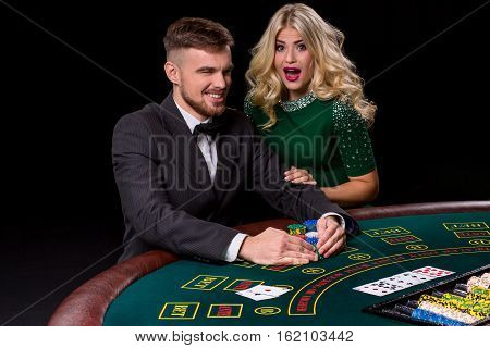 View of young, confident, man with the lady while he's playing poker game. The blonde looks into the camera