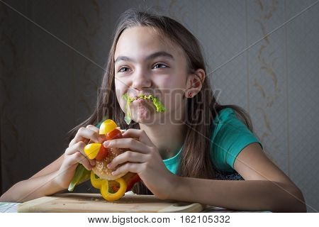 11 Year Old Girl Eating A Hamburger, Mouth Sticks Lettuce Leaf As A Mustache