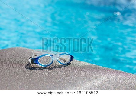 blue swimming goggles isolated on brown fabric chair and clear blue water background with copy space