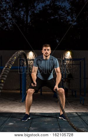 Young man in sportswear training with ropes. Athlete Outdoors