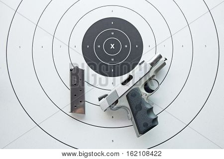silver .45 pistol with magazine in safety position on bullseye target paper from top view