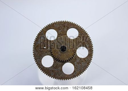 old, rusty gear which made five holes on a white background