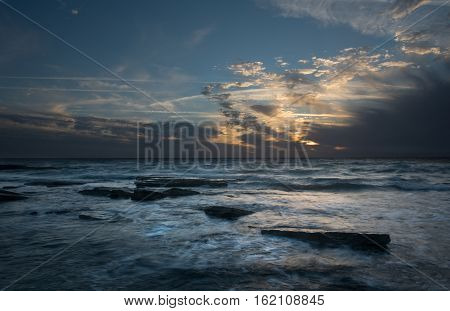 Rocky beach with seawaves crashing at the rocks during sunset