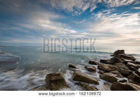 Rocky beach with Sea waves flowing through the rocks. Episkopi Limassol Cyprus