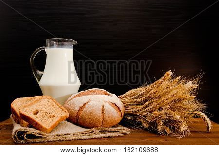Jug of milk round rye bread a sheaf of wheat and bread slices on sackcloth wooden table