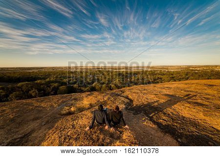 The couple enjoy the scenery view on the top of the wave rock Hyden Western Australia sunset scene .