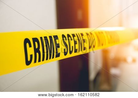 crime scene tape in front room door with flare and vintage tone
