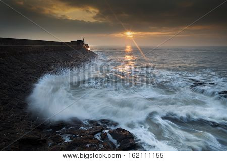 Sunrise at Porthcawl Sunrise and a choppy sea at Porthcawl lighthouse in South Glamorgan, South Wales