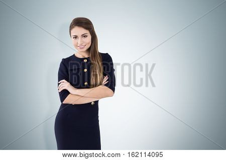 Portrait of a woman with long brown hair smiling charmingly and standing with her arms crossed near a gray wall. Mock up