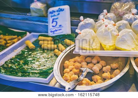 Spring Rolls on a banana leaf and Balls with price tag at Thai street night market. Deep fried snacks with different fillings and thai sauce in packets fresh and hot food