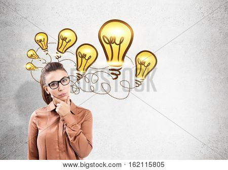 Portrait of a serious bespectacled woman standing with her arm on her chin near a concrete wall with a light bulb sketch. Mock up