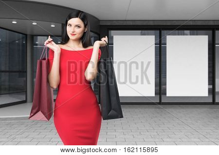 Close up of a woman in a bright red dress is standing with two shopping bags near a mall entrance. Concept of consumerism. 3d rendering. Mock up.