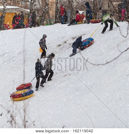 Children playing in snowy winter park. Selective focus. Concepts of active lifestyles, winter amusement, tobogganing, Christmas, New Year.
