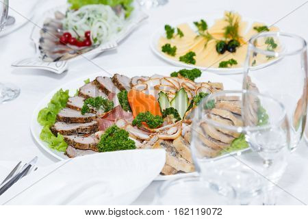 Cutlery and cold cuts served on a festive table in restaurant