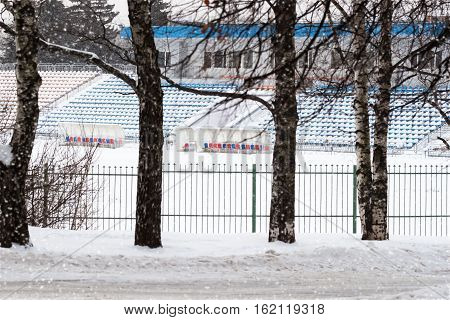 Winter empty stadium. Football field and seats for the teams and spectators covered with snow