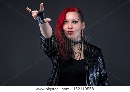 Informal woman with devil horns gesture on gray background