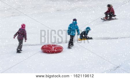 Children are sleding from the hill in one of snowy park, winter leisure, active lifestyles, tobogganing, Christmas. Selective focus. With place for your text, for background use.