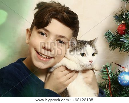 teen boy with cat and christmas tree close up portrait