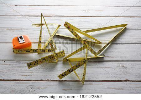 Broken Measuring Tape on Wooden Textured Background