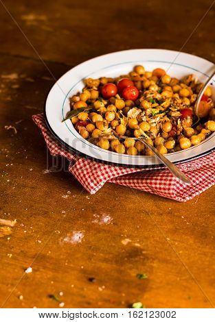 Portion of chickpea stew with cherry tomatoes, roasted chicken, capers and lemon zest in plate on a wooden table, selective focus