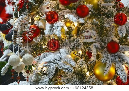 Beautiful Christmas background - christmas tree close-up decorated with christmas balls and snow. Happy new year!