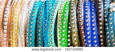 The row of many multicolored bracelets close up banner fashion background