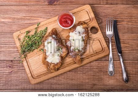 Baked chicken parmesan on the wooden board.