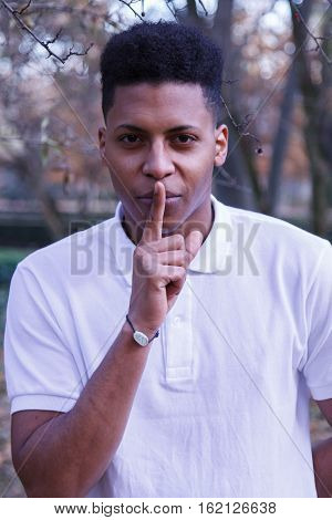 Young black African man sending silence. He puts his finger to his lips as a gesture to silence.
