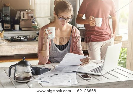 People family and finances. Young beautiful wife wearing rectangular glasses doing paperwork sitting at kitchen table with papers laptop and calculator on it having focused and frustrated look poster