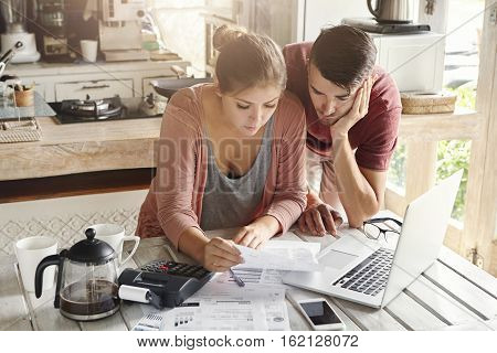 Young Stressed Family Paying Utility Bills Online Using Laptop. Worried Woman Holding Document, Calc